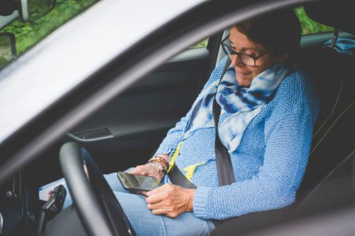 A woman sits in the passenger seat of a car and looks at her smartphone mobile Woman Sit using employed smile Telephone mobile phone Technology