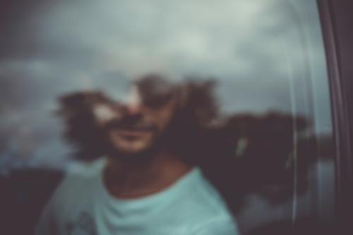 A man looks out the window of a car. Blurry. Man Transport Slice peep out hazy blurred Clouds reflection Pane Window Window pane look out experimental portrait