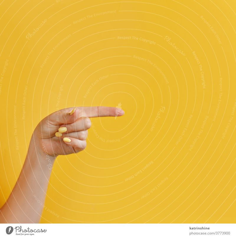 Close up of female hand pointing away on yellow background monochrome bright woman faceless closeup concept copy space negative space Gesture Arm Sign Nonverbal