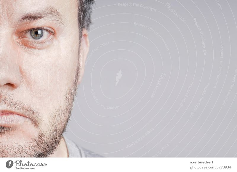 half face of serious mid adult man looking at camera with copy space real people age aging beard middle aged portrait graying mature male one person caucasian