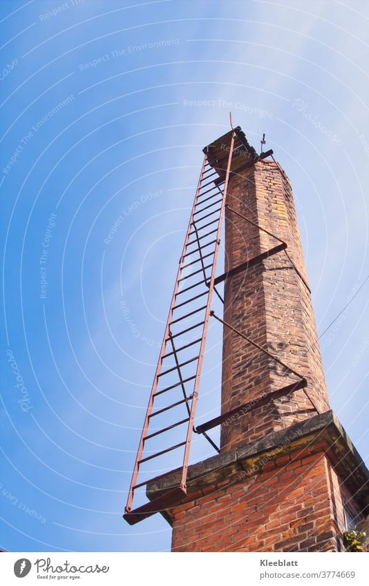 Old factory chimney made of red bricks with rusty ladder rises into the blue-white sky - Lost Place Factory fireplace Architecture Exterior shot Wall (barrier)
