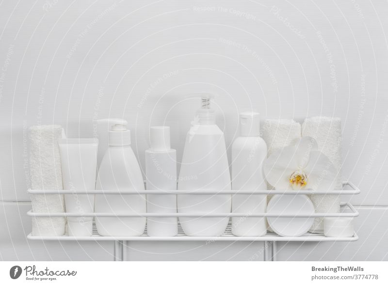 White bottles of cosmetic beauty products in bath Product hygiene care mockup unbranded closeup white background copy space many home shelf organizer wall tube