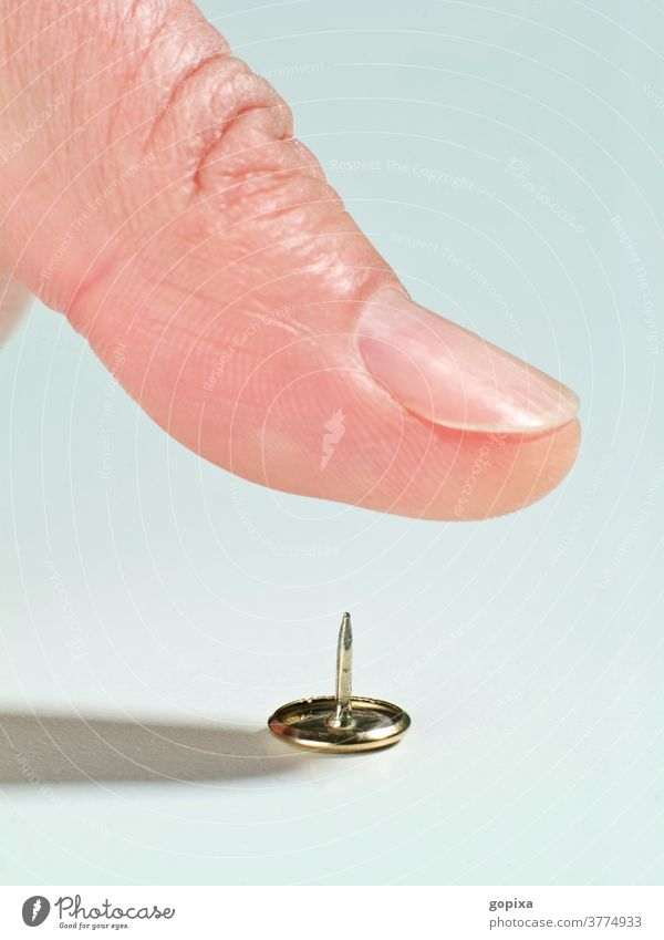 Close-up of a thumb over a thumbtack drawing pin Thumbtack Fingers peril violation Risk of injury Human being fingernails Macro (Extreme close-up) risky