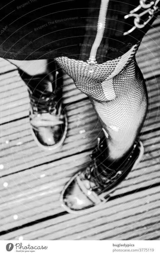 Woman photographed from the hip downwards in standing position. She wears a black skirt with a conspicuous zipper and chains, fishnet tights with runners and holes and rough black shoes. The focus is on the big running stitch.