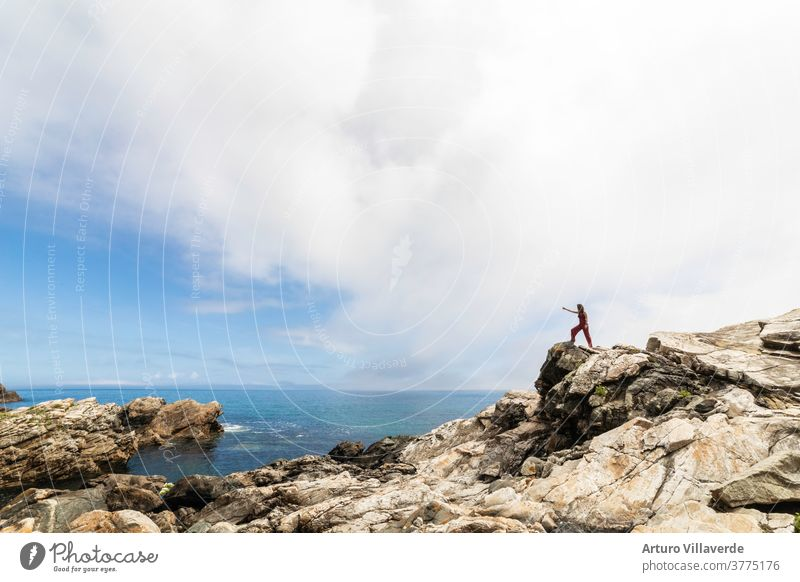 general shot of the Galician coast with a woman perched on some rocks observing the horizon sea traveler mountain freedom summer landscape sunset backpack