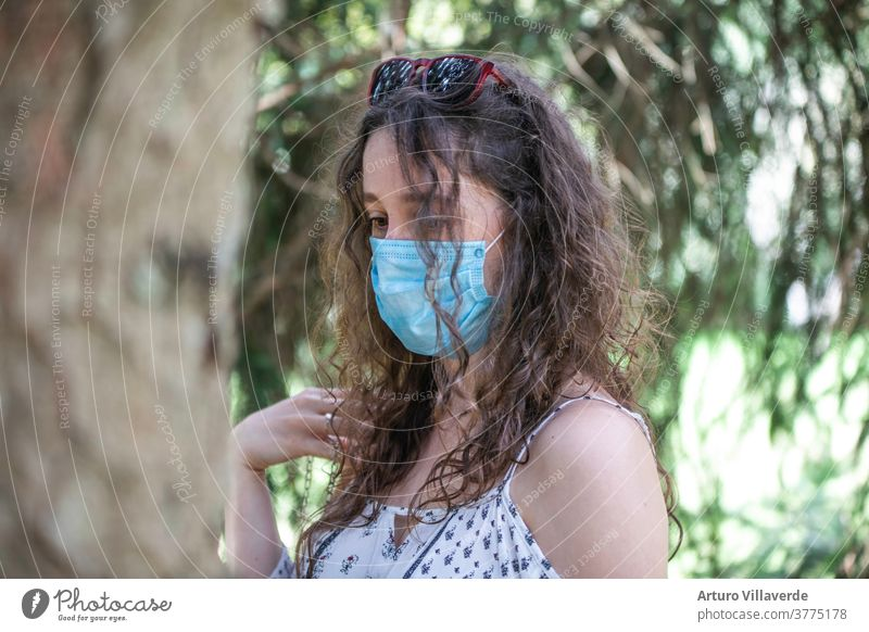 portrait of a young girl with a mask walking among trees quarantine garden outdoor health covid-19 coronavirus park epidemic prevention pandemic outdoors