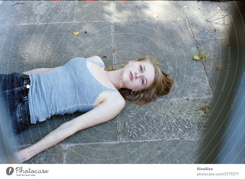 Portrait of a young woman lying on the floor and looking up through bars into the camera Woman Young woman Slim already athletic Blonde youthful 18-25 years