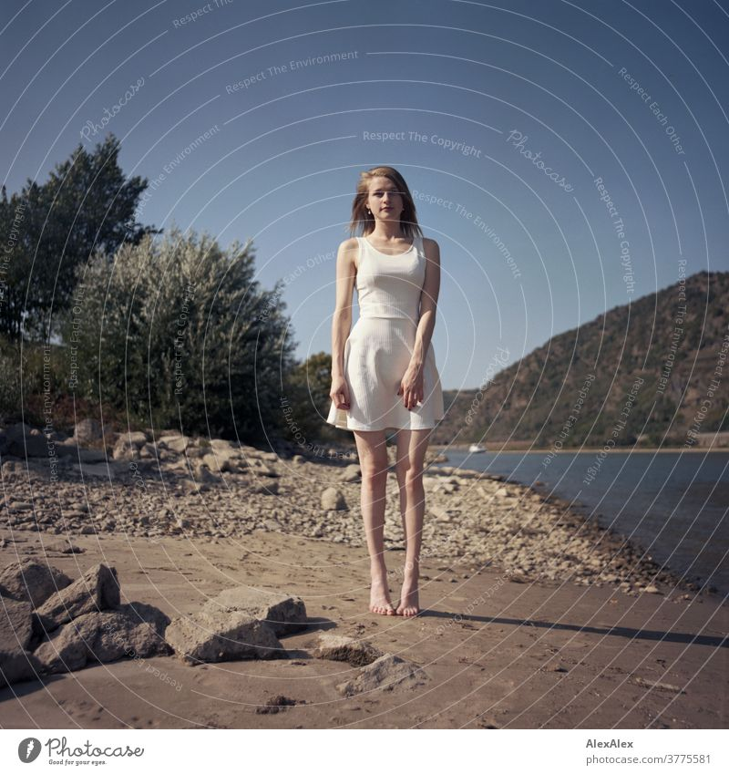 Analogue portrait of a young, barefoot woman standing on the banks of the Rhine Woman Young woman Slim already athletic Blonde youthful red blonde hair look see