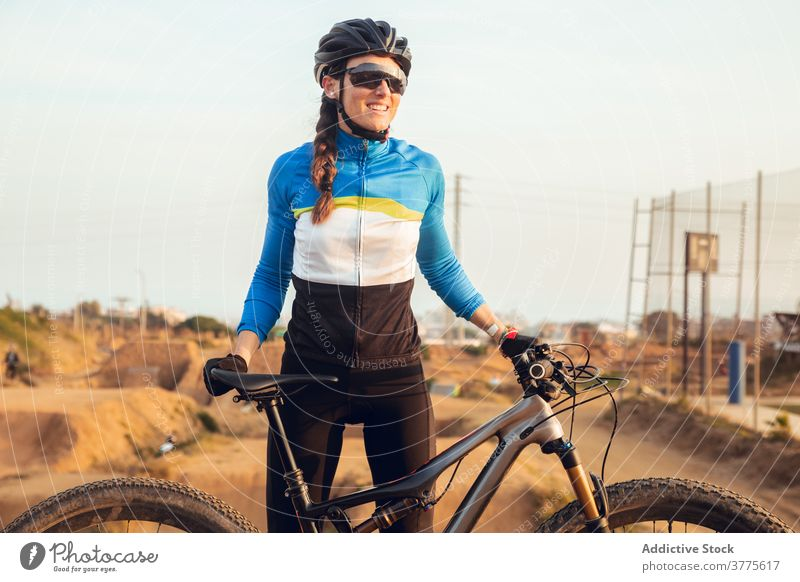 Sporty young woman in helmet with bicycle looking at camera smiling mountain bike trial cyclist trick sportswoman biking cycling sportswear riding glasses