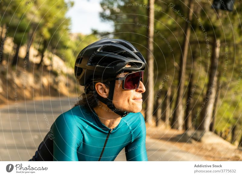 Woman road bike horizontal woman young adult mature woman driving sunset 40 years motion people riding sport athlete athleticism color image cycling headwear