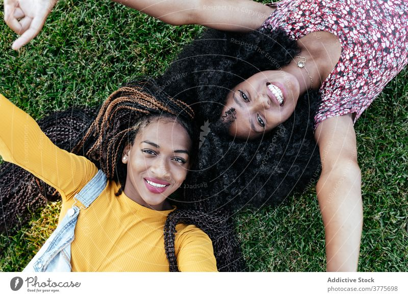 Happy black women lying on green grass friend together happy cheerful summer enjoy friendship girlfriend young african american ethnic afro female student smile
