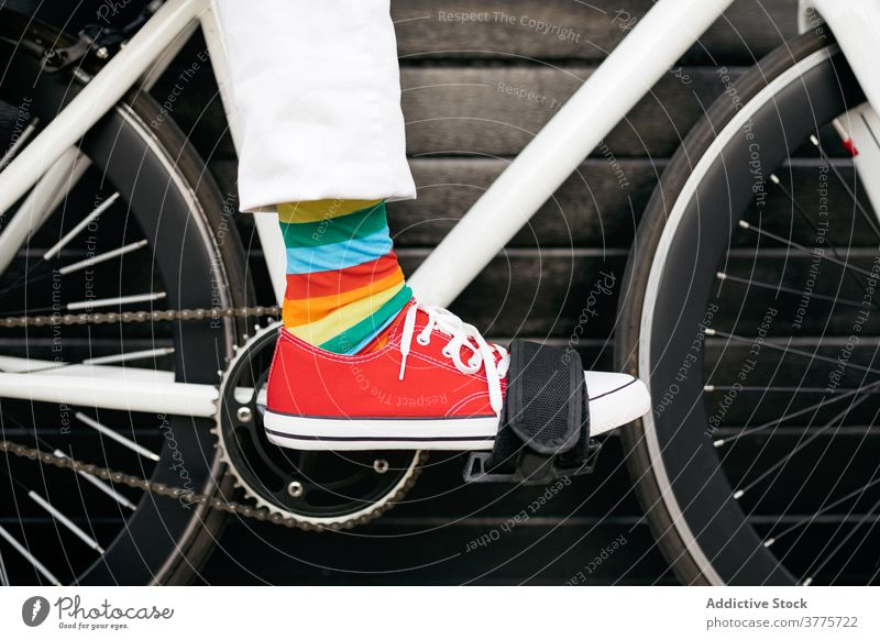 Crop person in colorful socks on bicycle stripe rainbow creative fun bike vehicle modern city street urban style trendy transport town hipster outfit cool