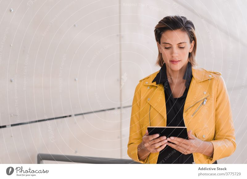 Woman on tablet near building woman city using style female content gadget device communicate modern urban casual street connection lady trendy town joy delight