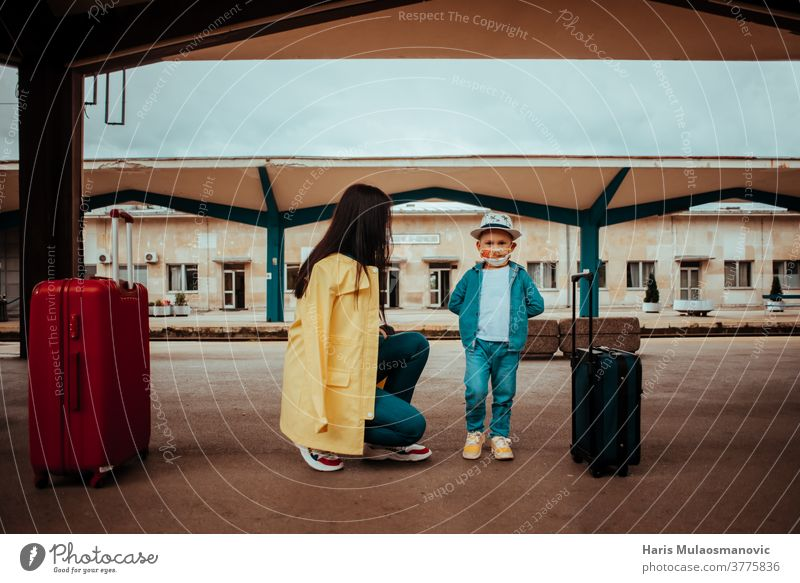 Mother and child traveling with face mask on railway station adult bag baggage bags beautiful caucasian city corona virus covid travel covid-19 destination