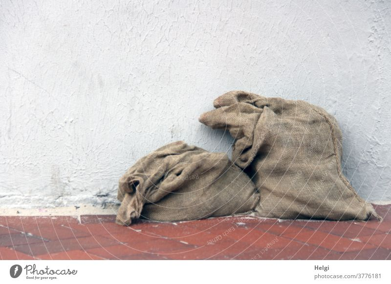 AST ;-) - two old partly filled jute bags on a red clinker floor leaning against a white wall Sack Jute sack 2 Stand Wall (building) White Red Brown Gray