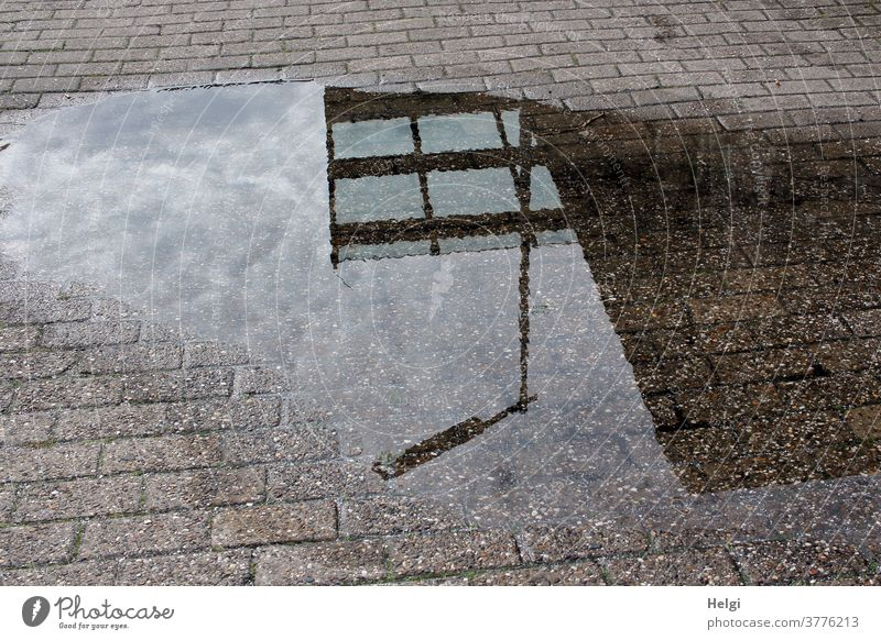 Lantern, glass roof and wall in front of a cloudy sky are reflected in a puddle reflection Puddle Paving stone Water Wet Glass roof Wall (building) Sky Clouds