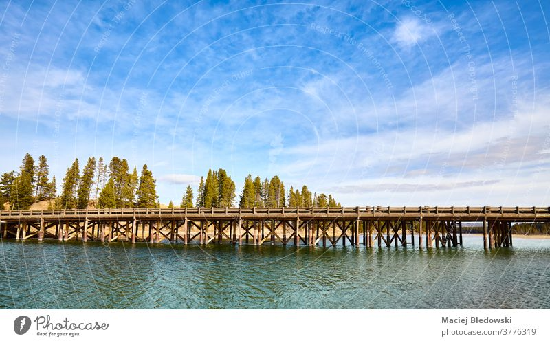 Fishing Bridge in Yellowstone National Park, Wyoming, USA. nature bridge travel landscape wooden scenic famous picture attraction lake river water sky America