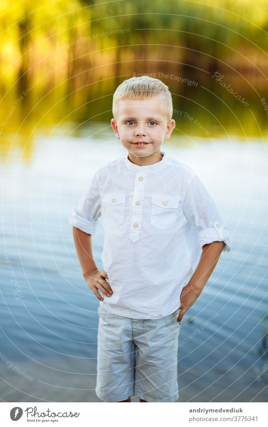Portrait of a happy and beautiful little boy with blond hair and a white shirt, Happy childhood. Positive emotion. portrait near the river in nature yellow
