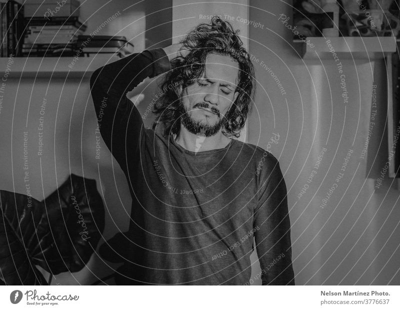 Black and white portrait of a hispanic man. He has long hair and he is standing in a corner of the livin groom. latin Black & white photo emotion cool hypster