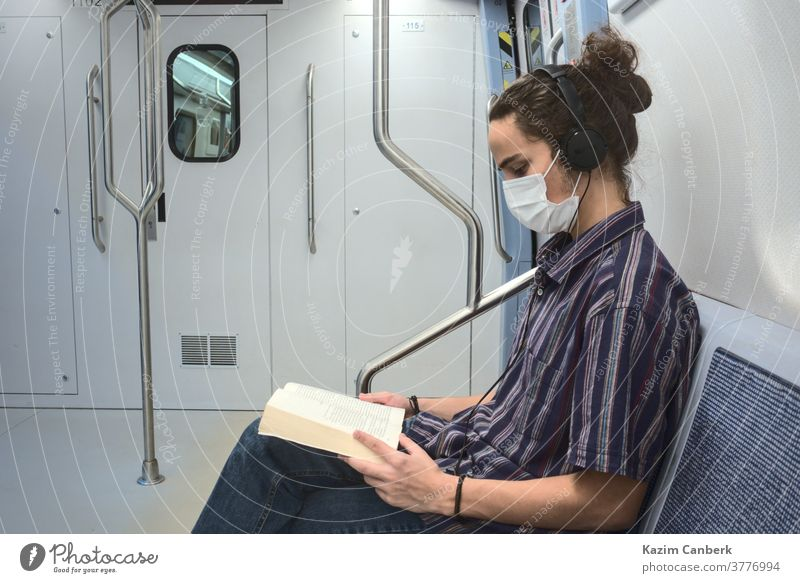 Concentrated masked millennial reading a book and listening to music in subway metro underground headphone sitting man young student teenager university college
