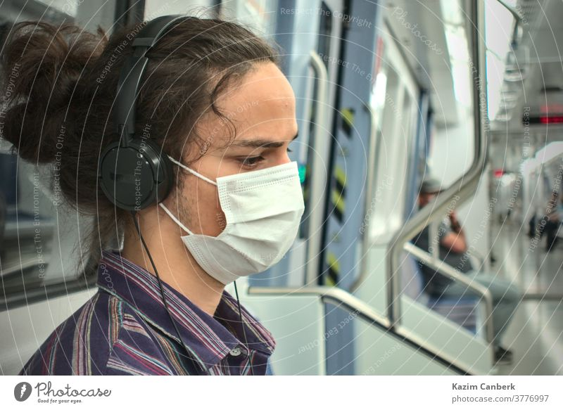 Masked sad looking teenager listening to music with headphone inside the subway metro underground mask smart phone sitting man young student millennial