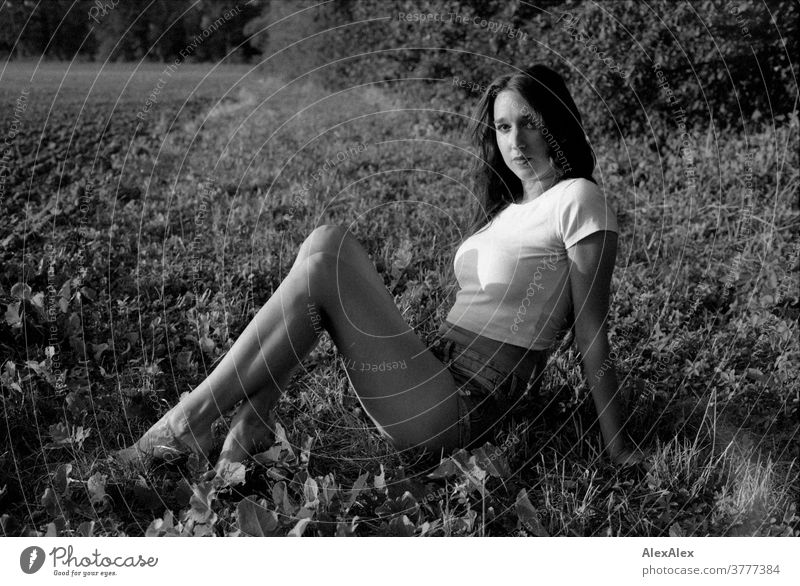 Black and white portrait of a young woman sitting in the grass in front of a forest at the edge of a field Woman already Near fit daintily Skin Face Blonde look