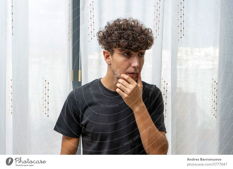 Attractive young man with curly hair wearing black t-shirt posing on white curtains background cheerful casual smile male adult handsome happy attractive