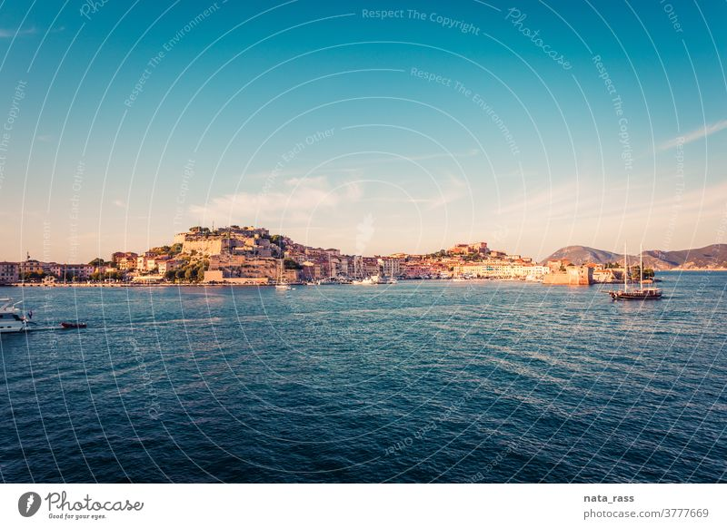 Panoramic view on Portoferraio ancient fortification in golden light on island Elba sunset architecture mediterranean port vacation lighthouse tuscan building