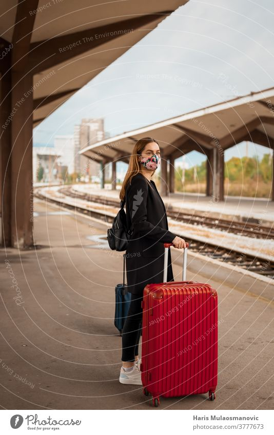 Woman with mask and travel bag waiting on public train station adult attractive baggage beautiful business caucasian city coronavirus covid-19 female journey