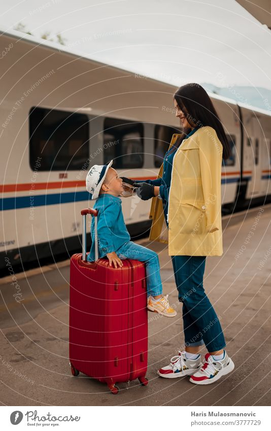 Mother and child with face mask and luggage bags, ready to travel adult baggage beautiful caucasian city corona virus covid travel covid-19 destination enjoy