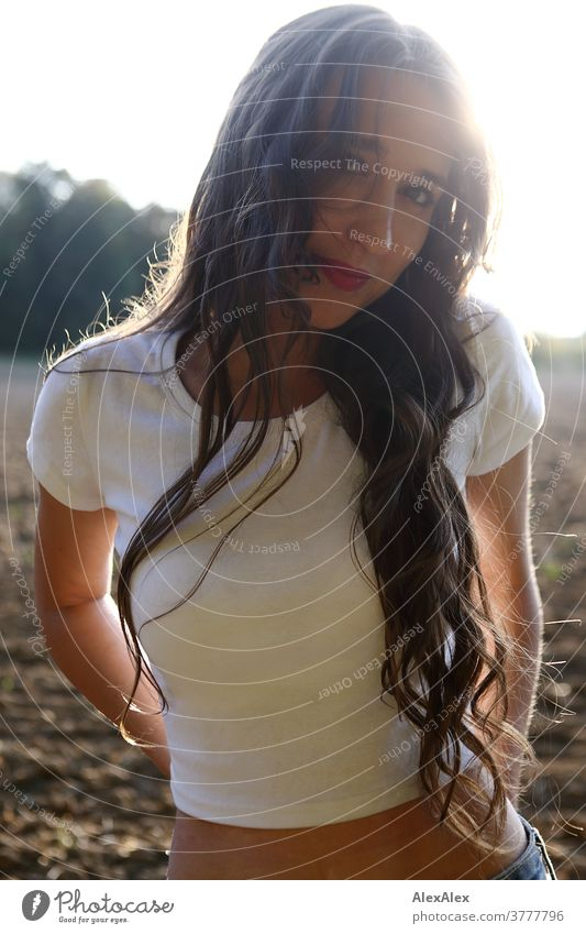 Backlit portrait of a young woman standing in front of a field and looking into the camera Woman already Near fit daintily Skin Face Blonde Direct Long-haired