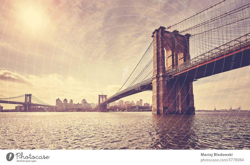 Vintage toned picture of Brooklyn Bridge against the sun, New York. city retro vintage building cityscape sunset river skyline bridge water USA urban East River