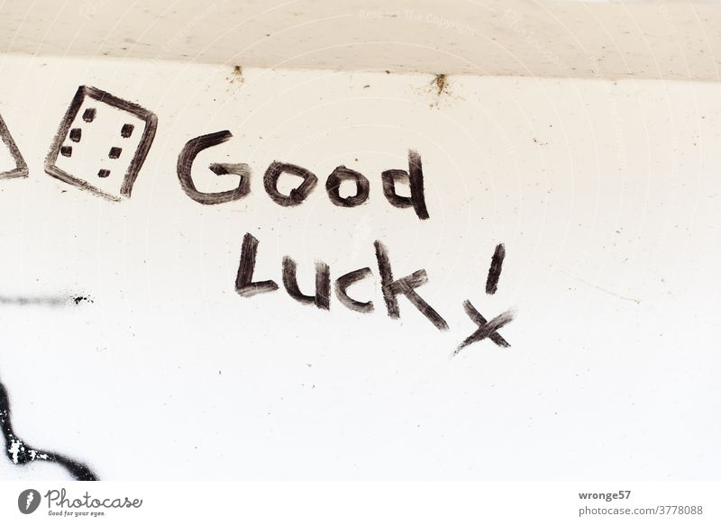 Good Luck ! written with black paint on a white wall Graffito writing authored good luck black color white background Colour photo Deserted Characters