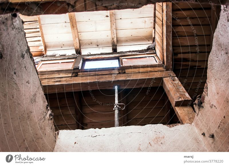 Supported wooden beam, above which a window lets light into the building site. Construction site wooden beams Wood construction masonry Architecture Old built