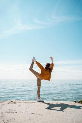 Young woman in a sweater on a beach practicing yoga Dancer's Pose (Natarajasana) yogini street cool training sportswear movement workout outdoors stylish
