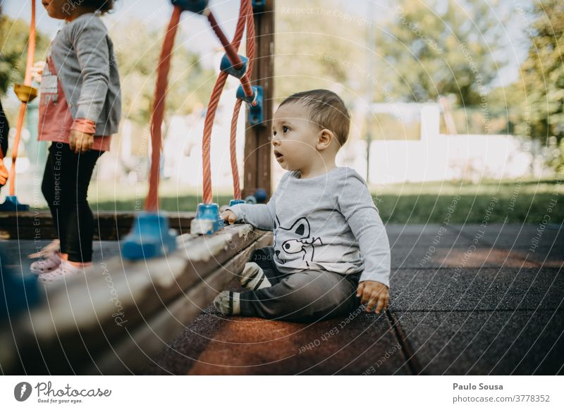Toddler playing at playground Caucasian Child Kindergarten Playing Playground Park Cute 1 Leisure and hobbies Infancy Exterior shot Joy Colour photo Human being