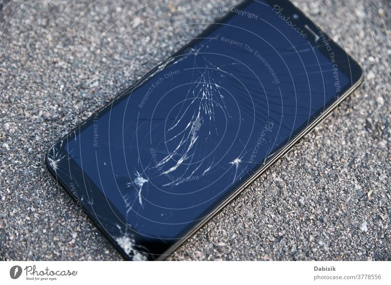 Damaged smartphone with broken touch screen on asphalt damage cell fall tablet floor mobile street crack smashed cellphone modern scratch ground electronic
