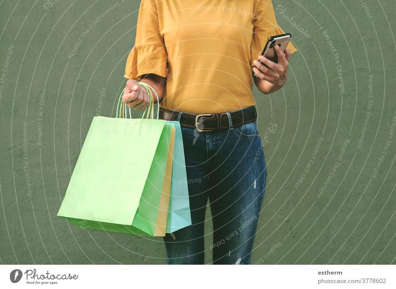 woman holding a shopping bags and smartphone young woman woman shopping shopper smile girl fun funny shopping center commerce shopping girl customer happy