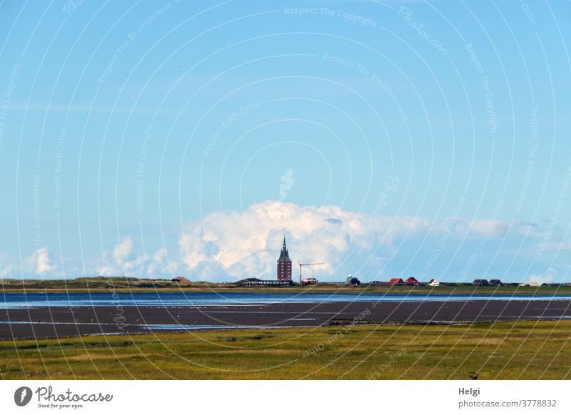Low tide in the mudflats - view over salt marshes and the Wadden Sea to the west tower of Wangerooge, behind which a thick cloud piles up in front of a blue sky