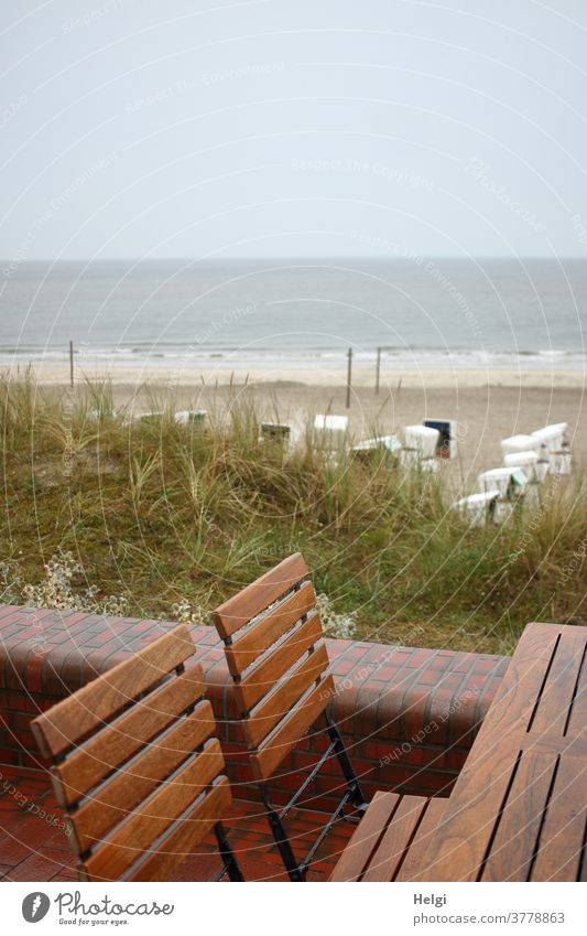 rainy day - empty wet chairs stand at the table on the beach promenade with a view of the beach with beach chairs and the rough North Sea Table dune Beach Sand