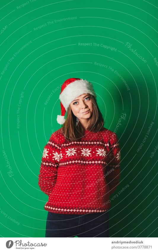 Young woman in Christmas sweater and Santa hat on green background. Isolated. winter chroma key smile holiday new year beautiful beauty caucasian celebration