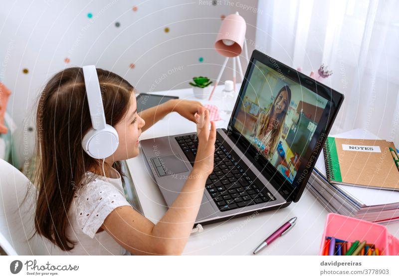 Girl watching online class of her teacher girl home schooling laptop waving online classes digital wisdom videoconference video call studying headphones happy