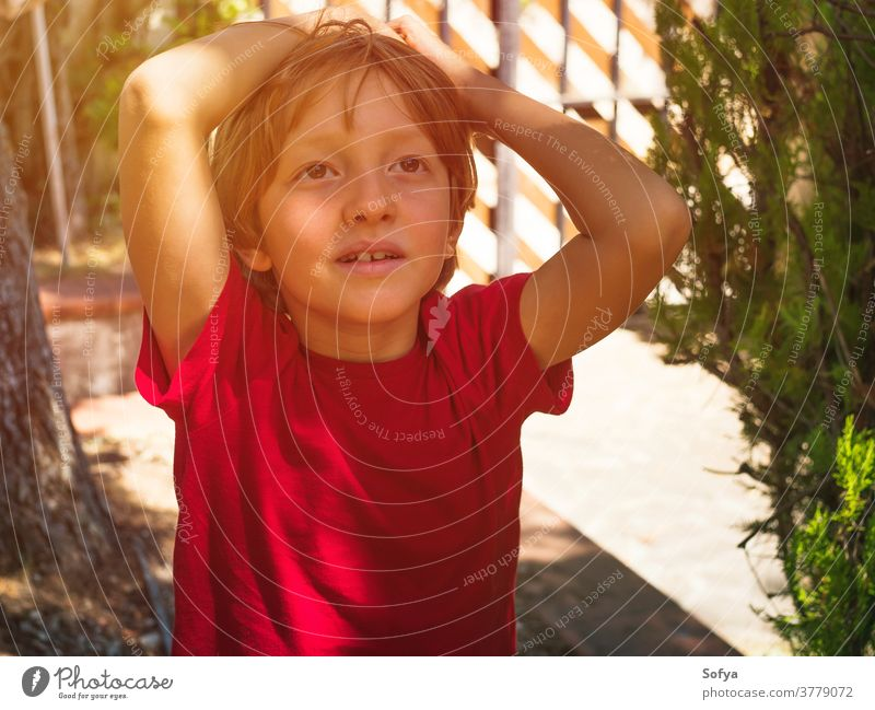 Little boy playing outdoors in summer lifestyle child authentic kid backyard freedom nature face smiling sun fun little portrait cute joy blonde sunlight