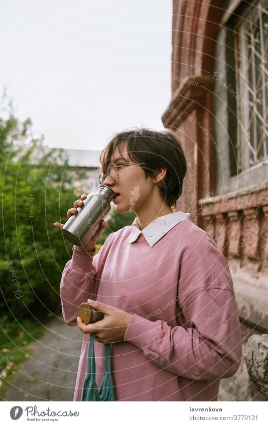 Young adult female with short hair drinking from metal sustainable water outdoors, selective focus bottle hands closeup fingers holding woman girl pink