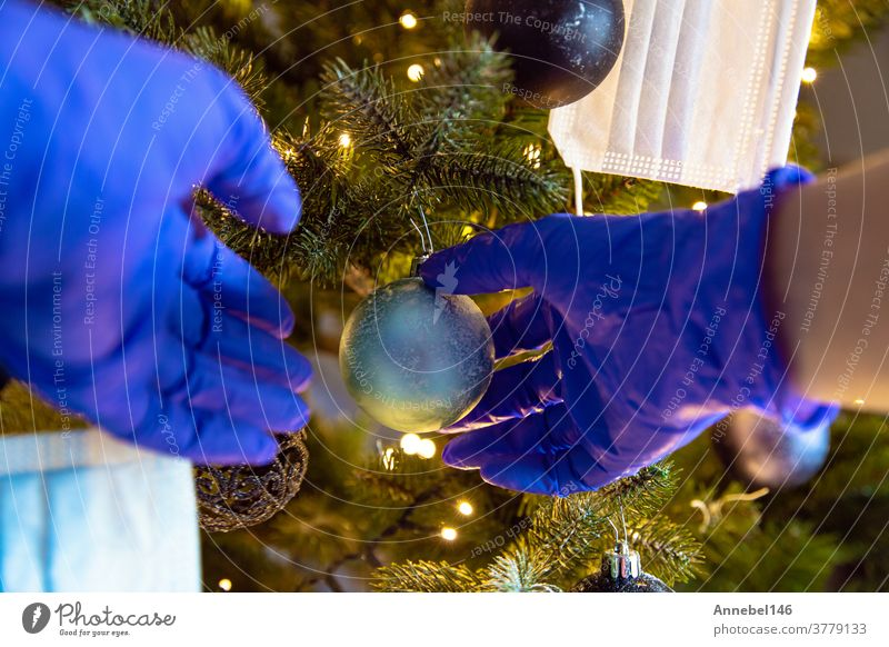 Person decorating a beautiful Christmas Tree with protective safety gloves for Covid-19, Concept for Coronavirus and Christmas Holiday hanging happy celebrating