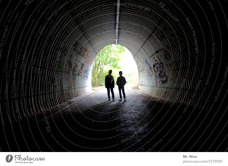 Silhouette of two young people in an underpass Tunnel Light Dark Graffiti Shadow Contrast Manmade structures Architecture Underpass Lanes & trails Pedestrian