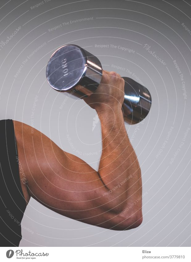 A muscular man with trained upper arms lifts a 10 kilo dumbbell. Focus on the biceps. Man Dumbbell chiselling Muscular Sports weight training Force Upper arm