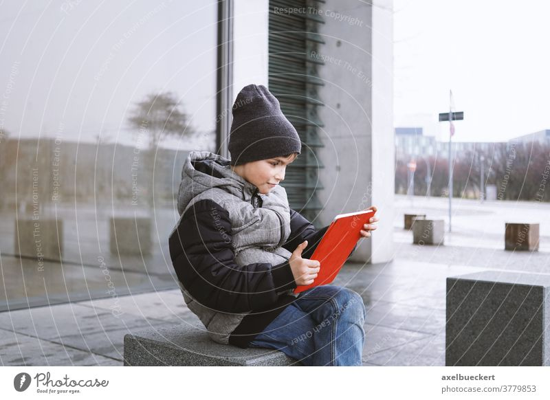 7 year old boy playing online game on tablet computer outdoors in winter child kid technology little people digital young fun internet childhood lifestyle
