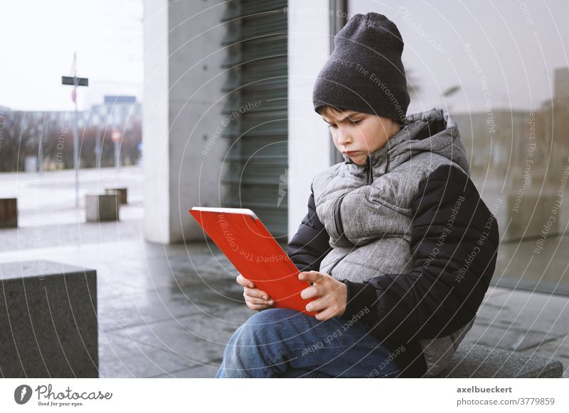 young boy looking at tablet pc computer with frustrated look on his face child kid play game technology little people digital internet childhood lifestyle