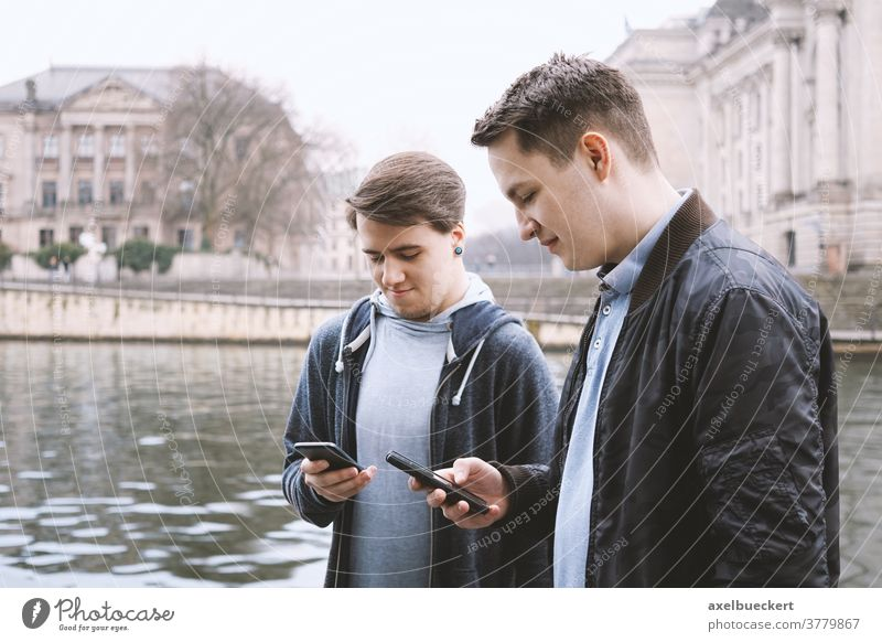 two mobile phone addicted male teenagers standing together looking at smartphone antisocial millennials young men friends using cell cellphone technology media